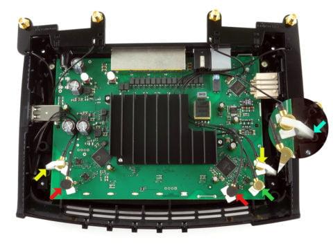 FRITZ!Box 7560: Die Klammern kommen auf die mit den gelben Pfeilen gekennzeichneten Murata-Stecker, die Moosgummi-Pads auf die mit rotem Pfeil. Der grün markierte Stecker bleibt frei und wird direkt vom Deckel gehalten.